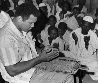 In this 1988 file photo, former world heavyweight boxing champ Muhammad Ali prays with a class of Muslim boys at Dafaalah el Sa'em Mosque in Khartoum, Sudan. As one of the most famous Muslims in the world, he traveled widely as a goodwill ambassador, spreading the message of Islam as a religion of peace. AP/Abder Raouf